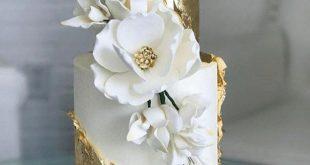 Edle Glamour Hochzeitstorte in Weiß und Gold mit ausgefallener Blumendekoration...